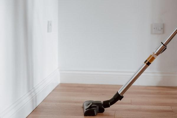 In einem Zimmer wird der Laminatboden mit einem Staubsauger gereinigt.