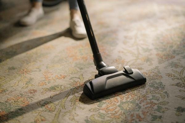 Jemand staubsaugt einen Teppich mit floralem Muster